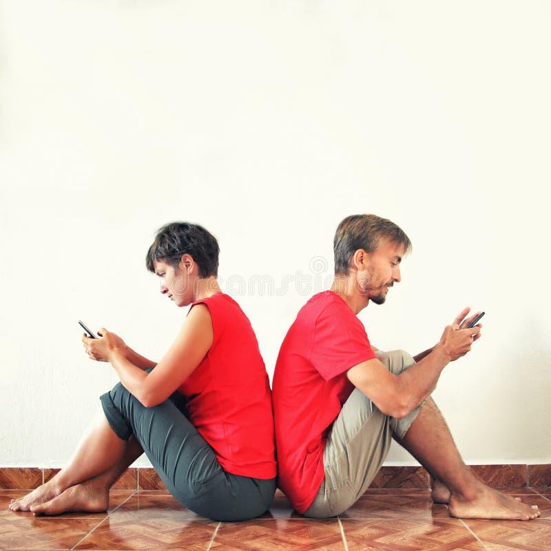 Uomo e donna che si siedono di nuovo alla parte posteriore e che esaminano i loro smartphones Gli aggeggi sostituiscono la comuni fotografia stock