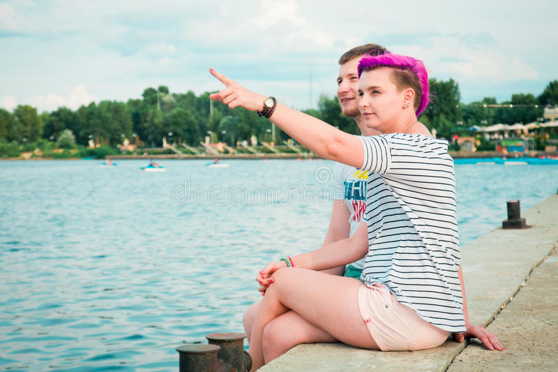 Uomo e donna che si siedono sulla sponda del fiume fotografia stock libera da diritti