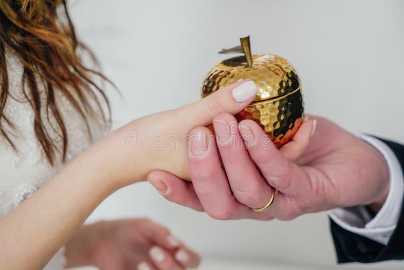 Uomo e donna che tengono mela dorata in loro mani come segno di amore, di Adamo moderno e di Eva, giorno delle nozze fotografia stock libera da diritti