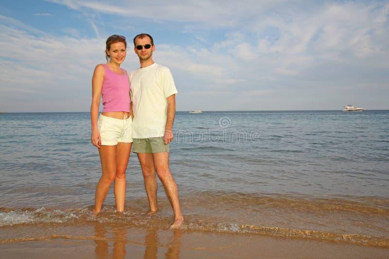 Uomo e donna circa il mare immagine stock