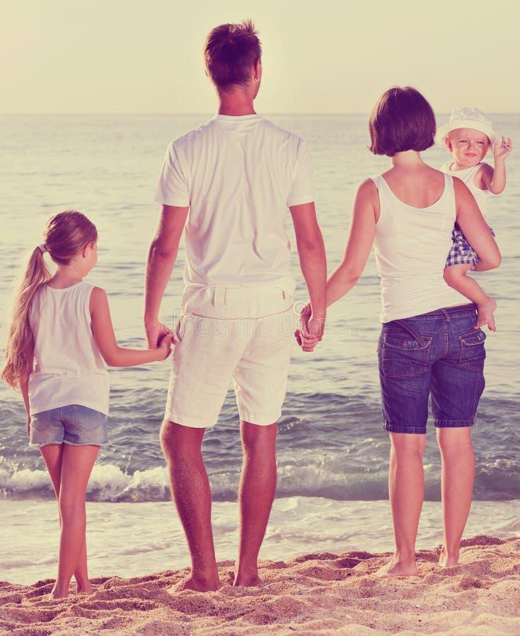 Uomo e donna con i bambini che stanno con di nuovo alla macchina fotografica su beac fotografie stock