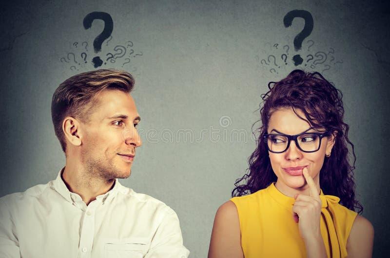 Uomo e donna con il punto interrogativo che se esamina con interesse immagini stock