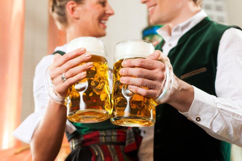 Uomo e donna con il vetro di birra in fabbrica di birra fotografia stock libera da diritti