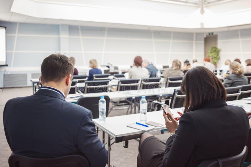 Uomo e donna con e la gente di affari che ascolta sulla conferenza o sull'addestramento nel corridoio immagine stock libera da diritti