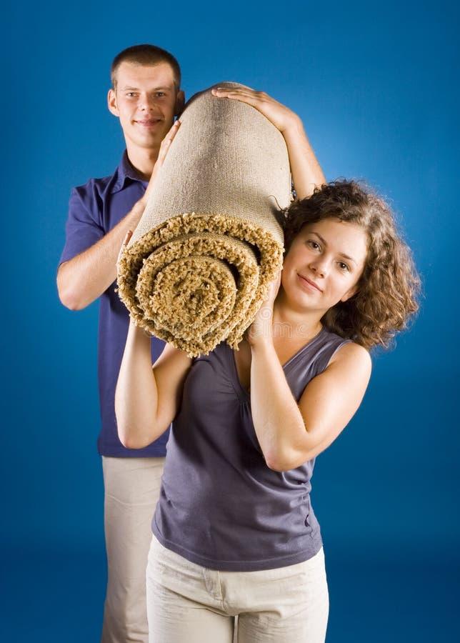 Uomo e donna con moquette rotolata immagine stock libera da diritti