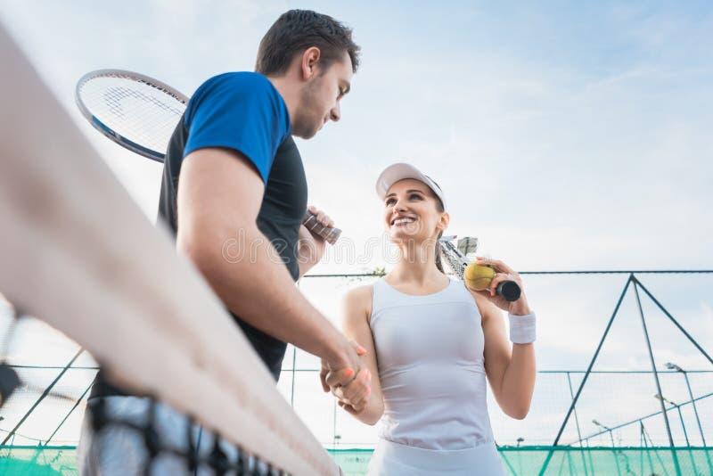 Uomo e donna del tennis che danno stretta di mano dopo la partita fotografia stock libera da diritti