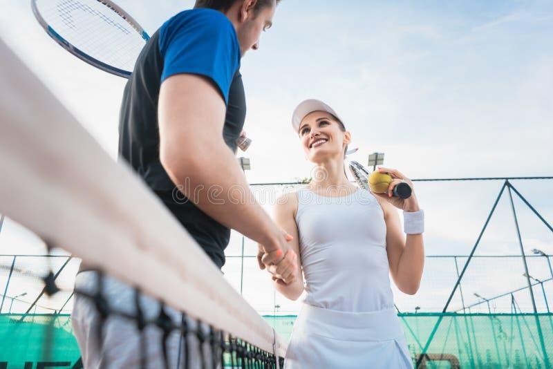 Uomo e donna del tennis che danno stretta di mano dopo la partita immagini stock