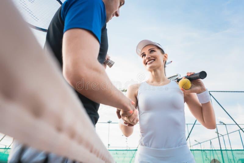 Uomo e donna del tennis che danno stretta di mano dopo la partita fotografia stock