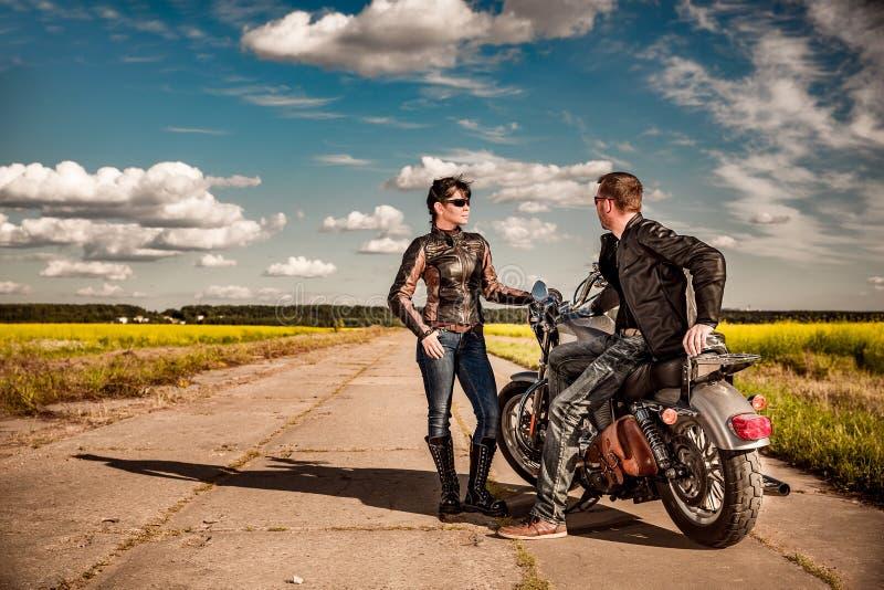 Uomo e donna delle coppie dei motociclisti vicino ad un motociclo sulla strada fotografia stock libera da diritti