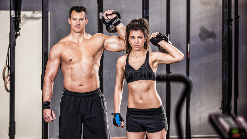 Uomo e donna di addestramento di Kettlebell in una palestra immagine stock