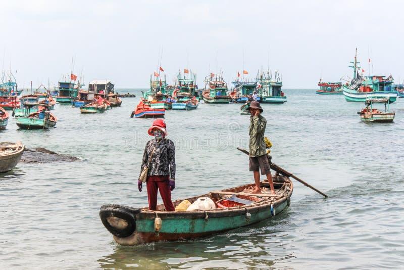 Uomo e donna di Fisher sulla barca di legno nel Vietnam immagine stock