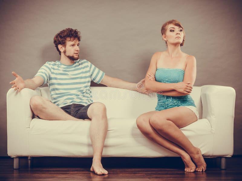 Uomo e donna in disaccordo che si siede sul sofà immagine stock