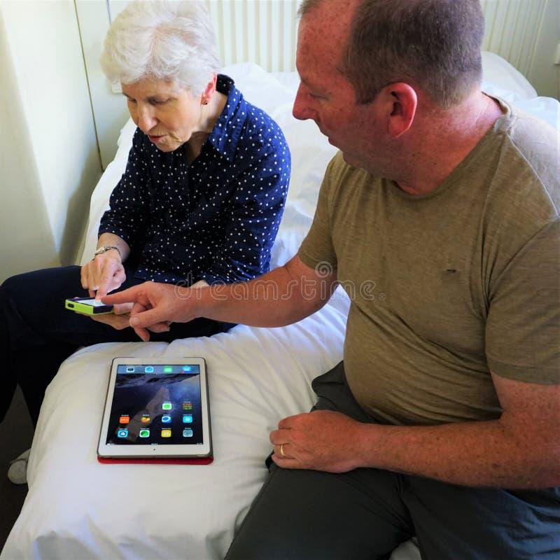 Uomo e donna discutere tecnologia del iPhone e del iPad immagini stock