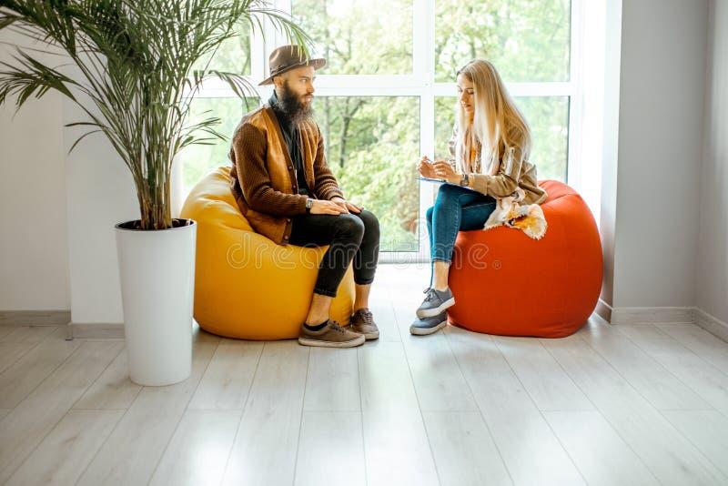 Uomo e donna durante il consiglio psicologico all'interno fotografia stock libera da diritti
