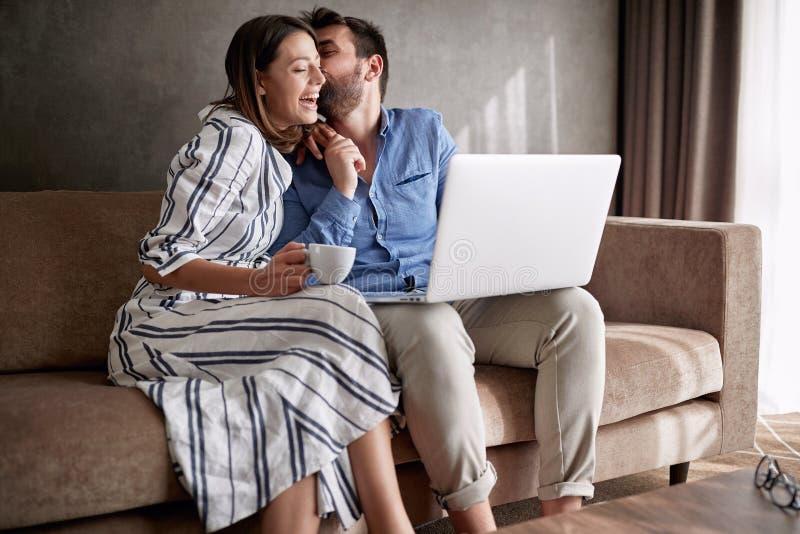 Uomo e donna felici divertendosi sul computer portatile di mattina con cof immagine stock