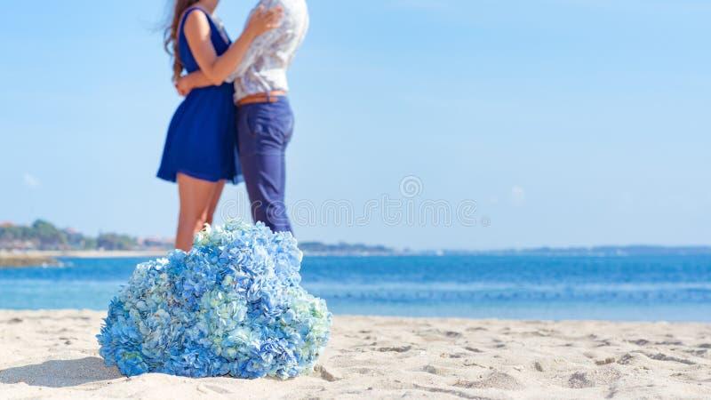 Uomo e donna insieme alla spiaggia con i fiori blu i a fuoco immagine stock