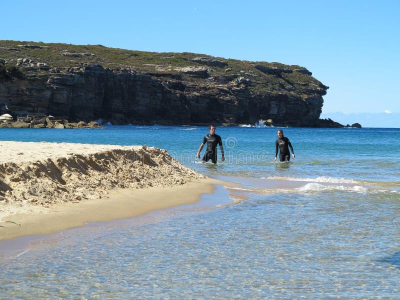 Uomo e donna naviganti usando una presa d'aria alla baia della spiaggia fotografie stock libere da diritti