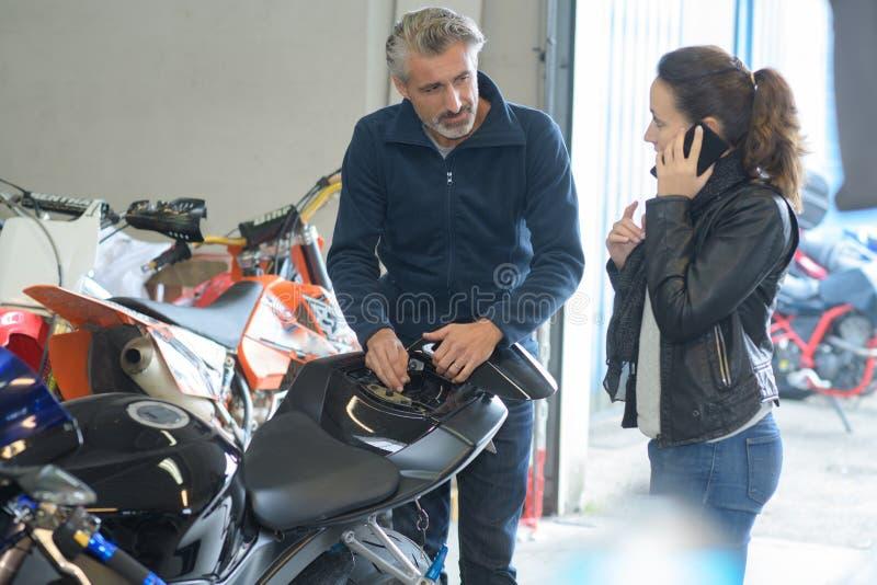 Uomo e donna nella donna del garage del motociclo sul telefono fotografia stock