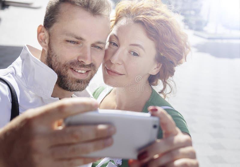 Uomo e donna sorridenti che prendono immagine se stessi sul cellulare, fondo della via Giorno, all'aperto fotografia stock