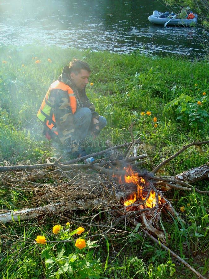 Uomo e fuoco di accampamento immagine stock