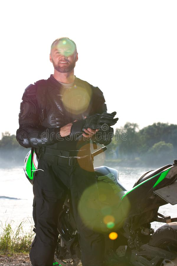 Uomo e motociclo del motociclista con il fondo del fiume, viaggio di moto del cavaliere sulla via alla riva del fiume, godente de fotografia stock libera da diritti