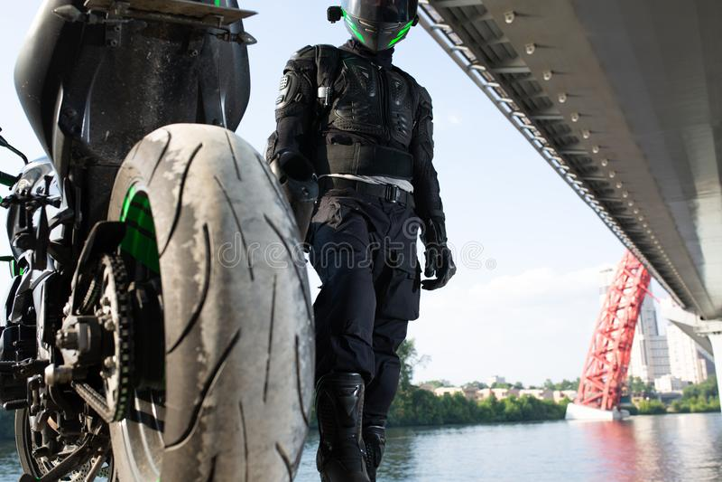 Uomo e motociclo del motociclista con il fondo del fiume, viaggio di moto del cavaliere sulla via alla riva del fiume, godente de immagine stock