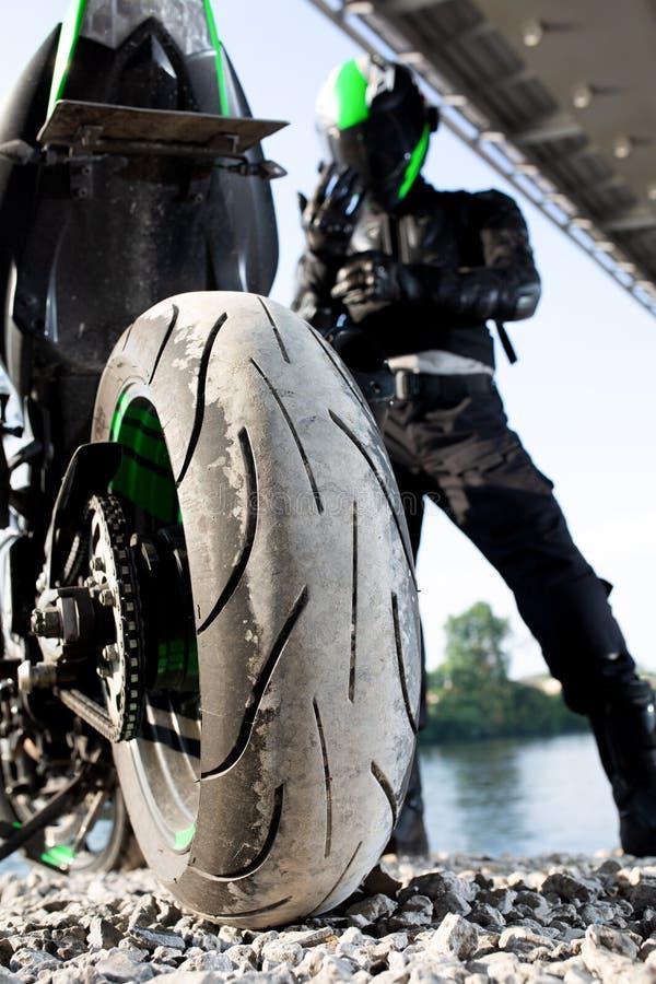 Uomo e motociclo del motociclista con il fondo del fiume, viaggio di moto del cavaliere sulla via alla riva del fiume, godente de fotografia stock