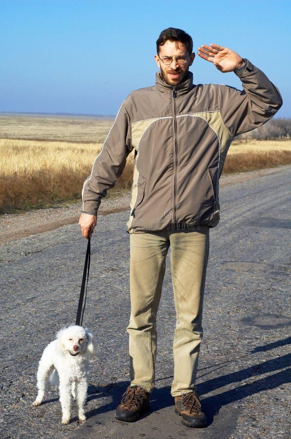 Uomo e piccolo cane bianco immagini stock