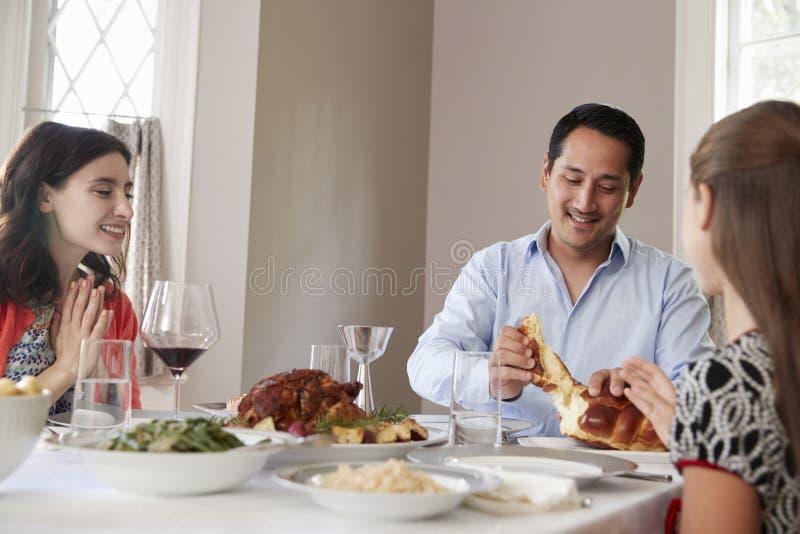 Uomo ebreo che divide il pane del challah con la famiglia al pasto di Shabbat fotografie stock libere da diritti