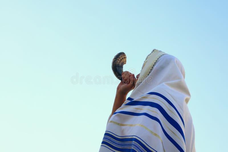 Uomo ebreo che soffia lo Shofar (corno) di Rosh Hashanah (nuovo anno) immagine stock libera da diritti