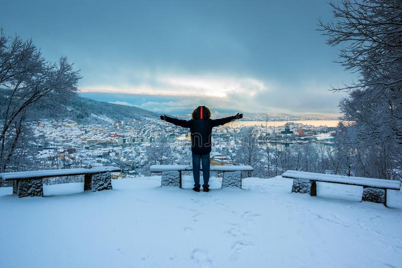 Uomo eccitato dalla bellezza di Snowy Bergen City Center nell'inverno al crepuscolo fotografia stock libera da diritti