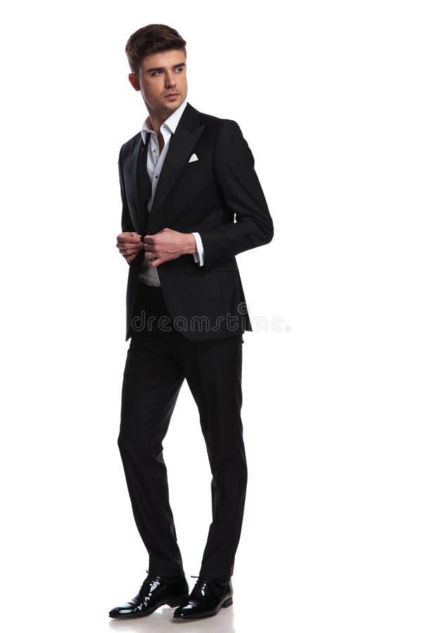 Uomo elegante che abbottona le suoi passeggiate e sguardi del vestito per parteggiare fotografia stock