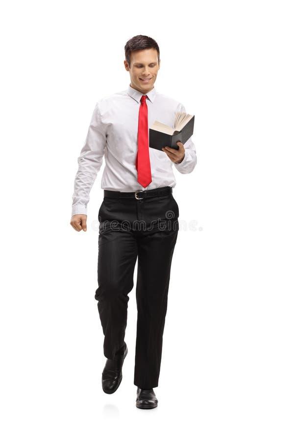 Uomo elegante che cammina e che legge un libro immagini stock