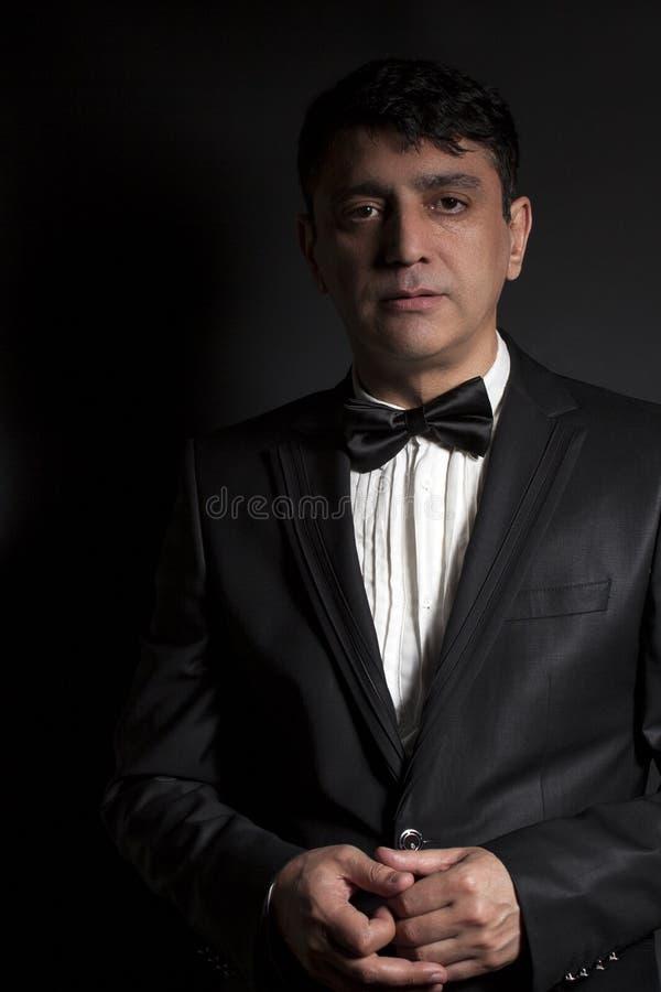 Uomo elegante che indossa farfallino nero e vestito nero fotografia stock libera da diritti