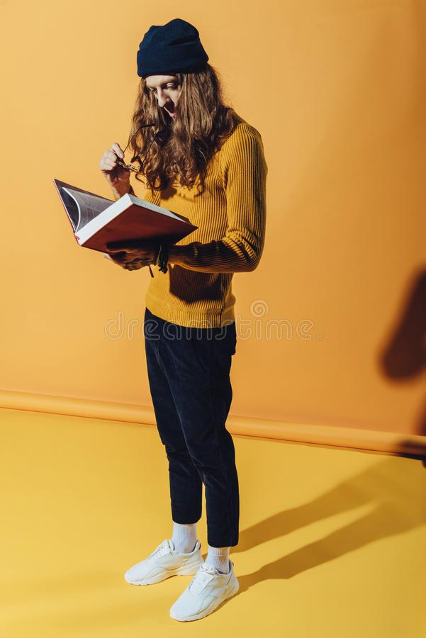 uomo elegante con il libro di lettura lungo dei capelli fotografia stock libera da diritti