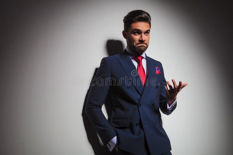 Uomo elegante confuso che gesturing e che fa un fa stupido indeciso immagini stock