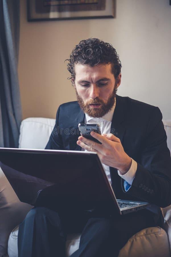 Uomo elegante dei pantaloni a vita bassa bei che per mezzo del computer portatile immagine stock libera da diritti