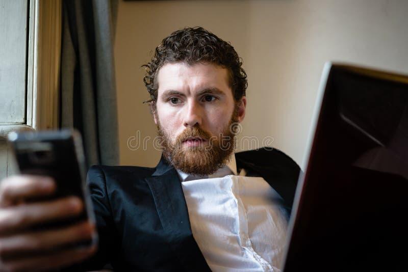 Uomo elegante dei pantaloni a vita bassa bei che per mezzo del computer portatile immagini stock