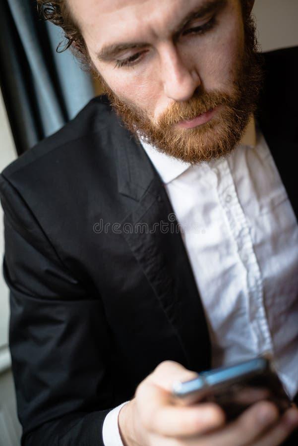 Uomo elegante dei pantaloni a vita bassa bei sul cellulare fotografia stock