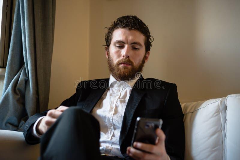 Uomo elegante dei pantaloni a vita bassa bei sul cellulare fotografia stock libera da diritti