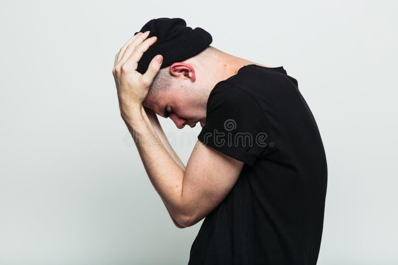 Uomo emozionale che possing con le mani sulla testa immagine stock