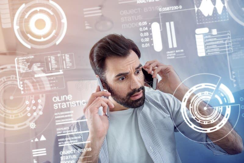 Uomo emozionale che preme due telefoni alla sua formica delle orecchie che sembra preoccupata immagine stock libera da diritti