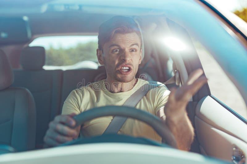 Uomo emozionale che ritiene furioso mentre guidando vicino al driver pericoloso fotografia stock libera da diritti