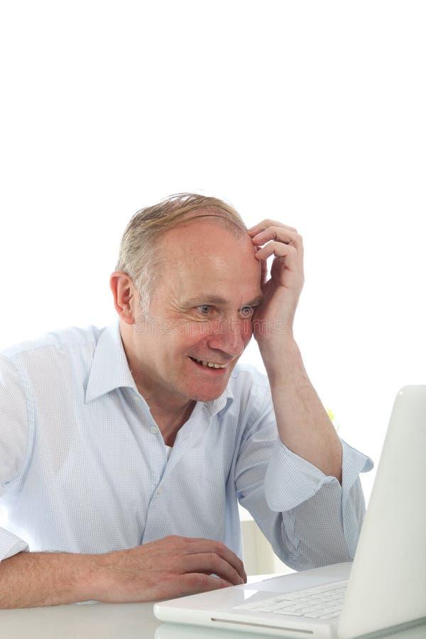 Uomo emozionante che legge il suo schermo del computer portatile fotografia stock libera da diritti