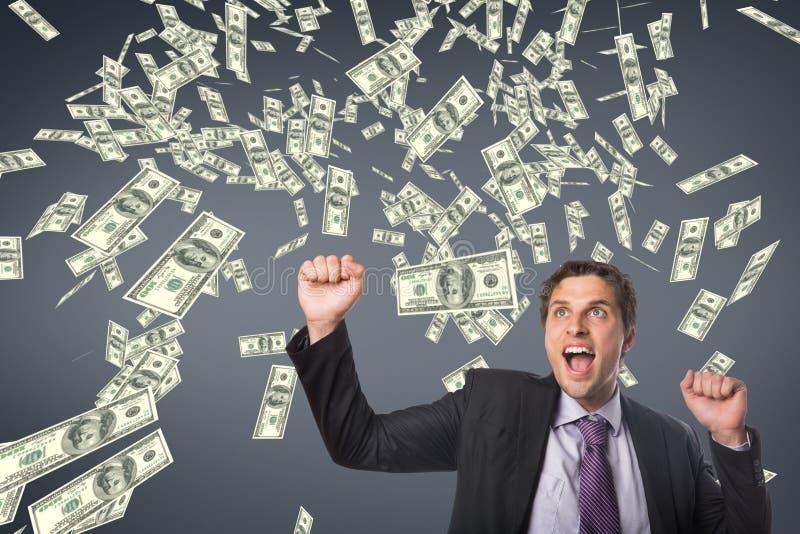 Uomo emozionante di affari con la pioggia dei soldi contro fondo blu fotografia stock libera da diritti