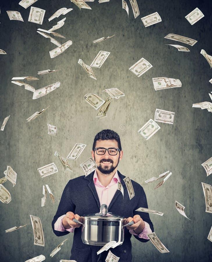 Uomo emozionante eccellente con la pentola del punto di ebollizione sotto la pioggia delle banconote in dollari dei soldi fotografia stock libera da diritti