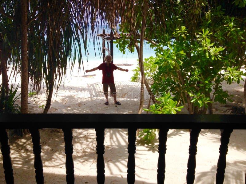 Uomo emozionante felice che sta la località di soggiorno di isola tropicale del chalet fronte mare anteriore immagine stock