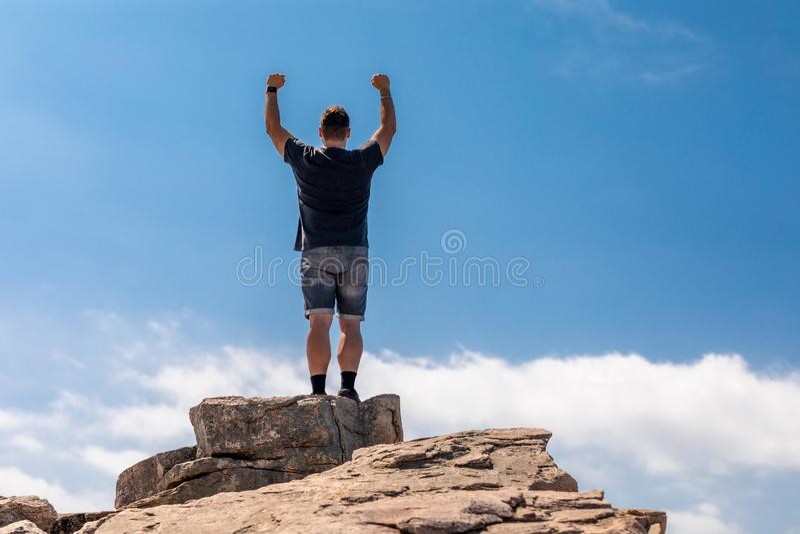 Uomo emozionante sulla cima in un bello paesaggio di estate fotografia stock