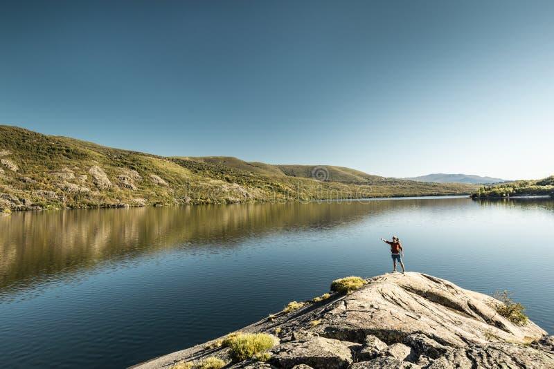 Uomo in escursionismo vicino a un bel lago fotografie stock libere da diritti