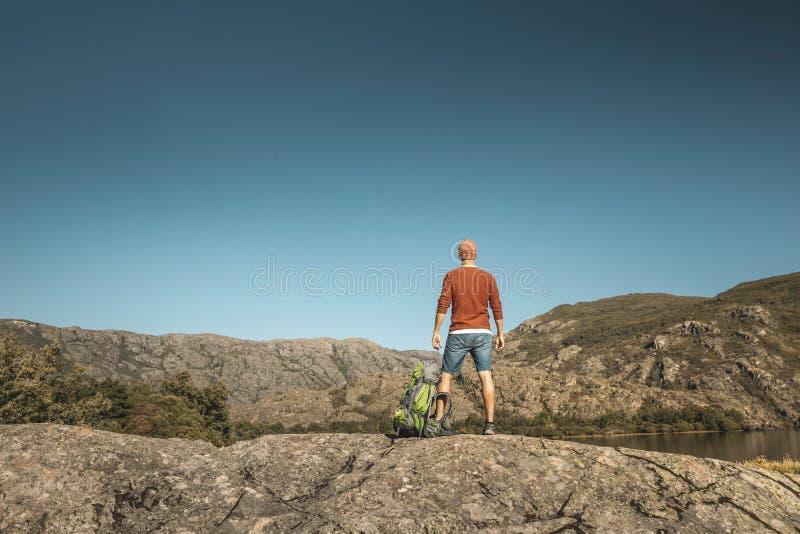 Uomo in escursionismo vicino a un bel lago fotografia stock libera da diritti